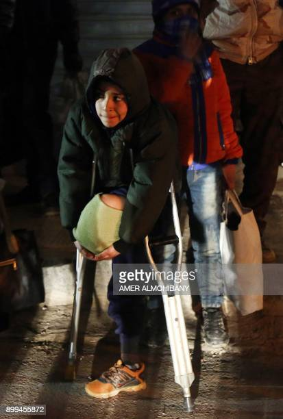 Tenyearold Syrian amputee Zuhair alGhazzawi waits in Douma to be evacuated by the Syrian Arab Red Crescent on the third night of an evacuation...