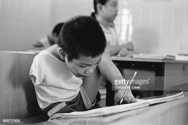 Tenyearold Tran Binh Minhn is handicapped as a result of the Agent Orange herbicide He writes with the aid of his left foot at the Peace Village in...