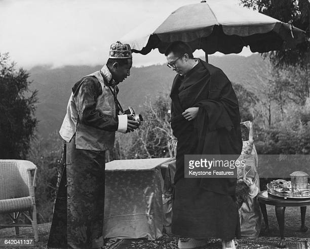 Tenzin Gyatso the 14th Dalai Lama shows interest in the camera held by Palden Thondup Namgyal the eldest son of Tashi Namgyal the Chogyal or ruler of...