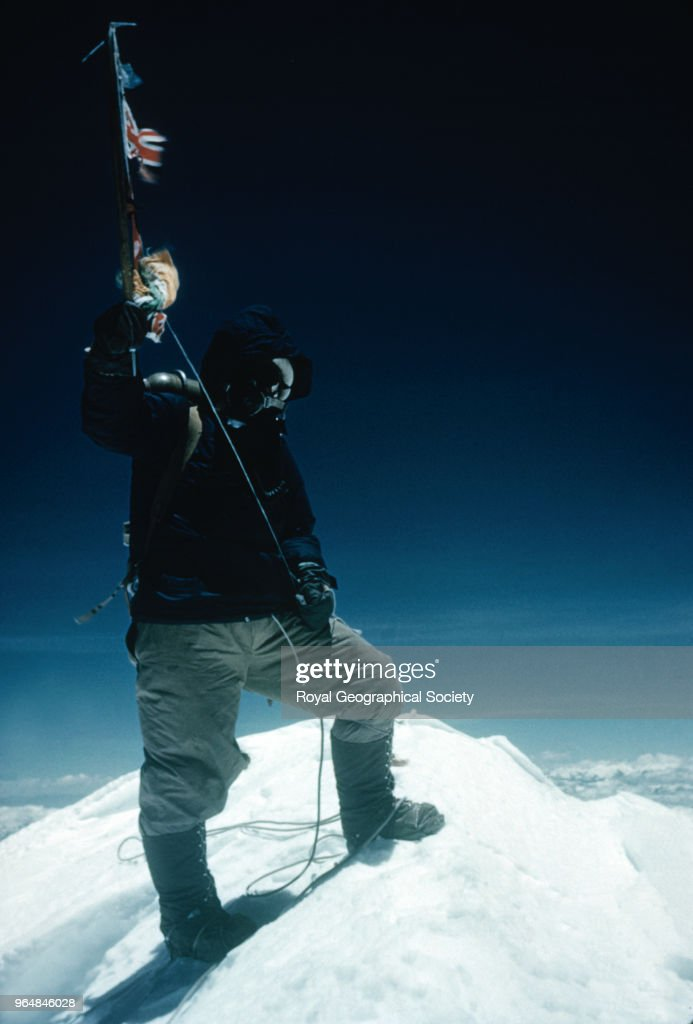Tenzing Norgay on the Summit of Mount Everest, Tenzing Norgay on the summit of Mount Everest at 11:30am on 29th May 1953. Tenzing waves his ice-axe on which are hung the flags of Britain, Nepal, the United Nations and India, Nepal, 29th May 1953. Mount Everest Expedition 1953.