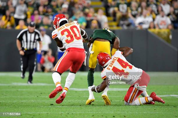 Teo Redding of the Green Bay Packers is tackled by Dorian O'Daniel and Harold JonesQuartey of the Kansas City Chiefs during a preseason game at...