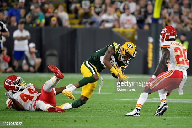 Teo Redding of the Green Bay Packers is tackled by Dorian O'Daniel of the Kansas City Chiefs in the second quarter during a preseason game at Lambeau...