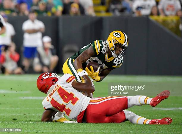 Teo Redding of the Green Bay Packers is tackled by Dorian O'Daniel of the Kansas City Chiefs during a preseason game at Lambeau Field on August 29...