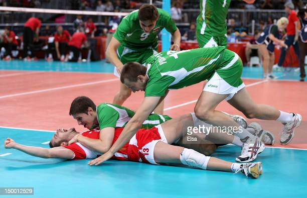 Teodor Salparov of Bulgaria is tackled by teammates Dobromir Dimitrov and Viktor Yosifov after they defeated Germany during the Men's Volleyball...