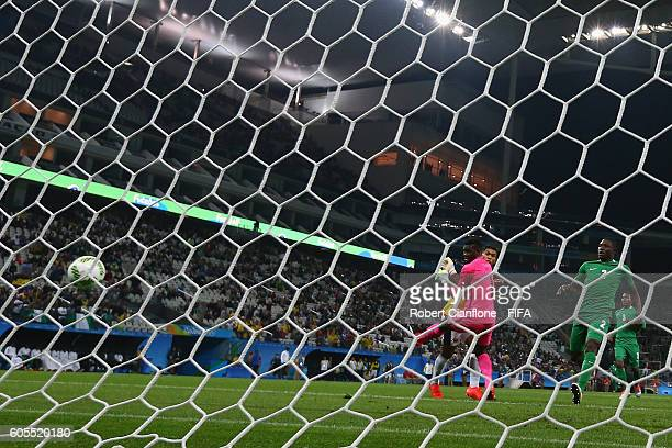 Teofilo Gutierrez of Colombia shoots past Nigerian goalkeeper Daniel Akpeyi to score during the Men's First Round Group B match between Colombia and...