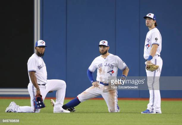 Teoscar Hernandez of the Toronto Blue Jays and Kevin Pillar and Randal Grichuk gather in the outfield during a pitching change in the sixth inning...