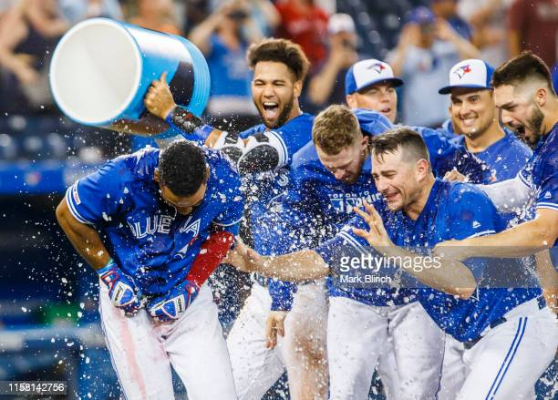 Teoscar Hernandez of the Toronto Blue Jays celebrates hitting his walk off home run with teammates against the Tampa Bay Rays in the 12th inning...