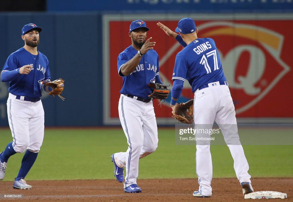 Teoscar Hernandez #36 of the Toronto Blue Jays celebrates their victory with Ryan Goins #17 during MLB game action against the Baltimore Orioles at Rogers Centre on September 11, 2017 in Toronto, Canada.