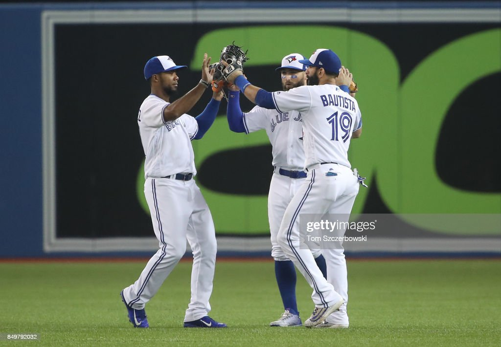 Teoscar Hernandez #37 of the Toronto Blue Jays celebrates their victory with Kevin Pillar #11 and Jose Bautista #19 during MLB game action against the Kansas City Royals at Rogers Centre on September 19, 2017 in Toronto, Canada.