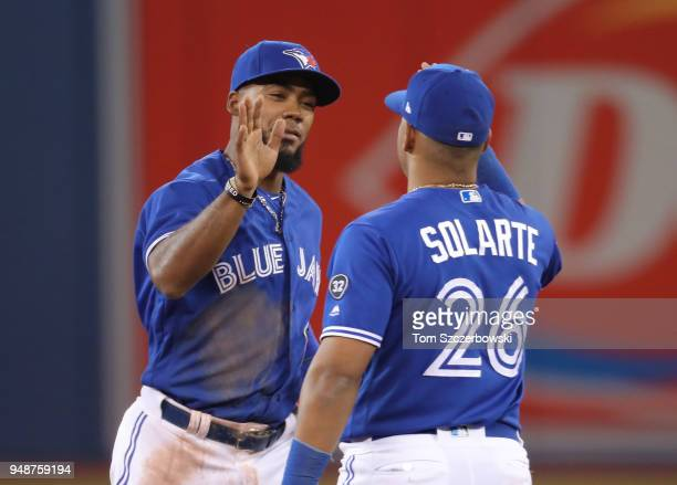 Teoscar Hernandez of the Toronto Blue Jays celebrates their victory with Yangervis Solarte during MLB game action against the Kansas City Royals at...