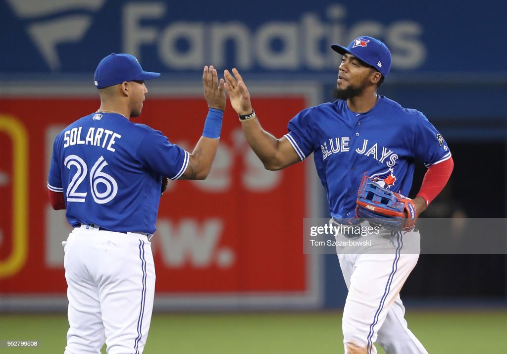 Teoscar Hernandez #37 of the Toronto Blue Jays celebrates their victory with Yangervis Solarte #26 during MLB game action against the Texas Rangers at Rogers Centre on April 29, 2018 in Toronto, Canada.