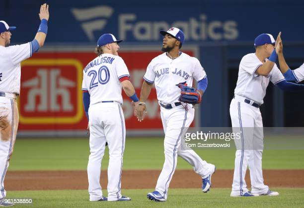 Teoscar Hernandez of the Toronto Blue Jays celebrates their victory with Josh Donaldson during MLB game action against the Los Angeles Angels of...