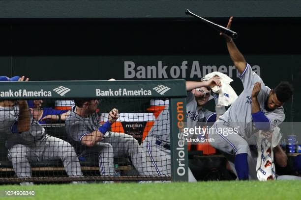 Teoscar Hernandez of the Toronto Blue Jays gets out of the way bat let go by batter Devon Travis against the Baltimore Orioles during the ninth...