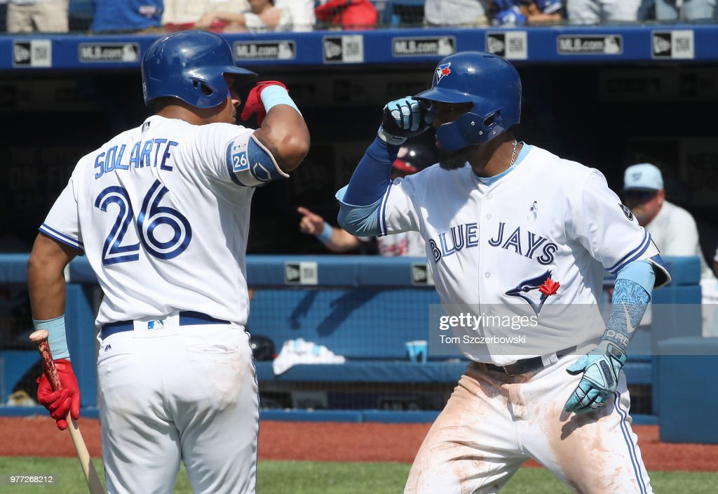 Teoscar Hernandez #37 of the Toronto Blue Jays is congratulated by Yangervis Solarte #26 after hitting a solo home run in the eighth inning during MLB game action against the Washington Nationals at Rogers Centre on June 17, 2018 in Toronto, Canada.