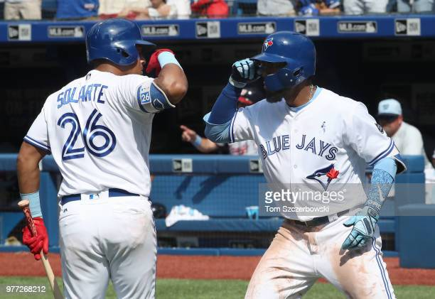 Teoscar Hernandez of the Toronto Blue Jays is congratulated by Yangervis Solarte after hitting a solo home run in the eighth inning during MLB game...
