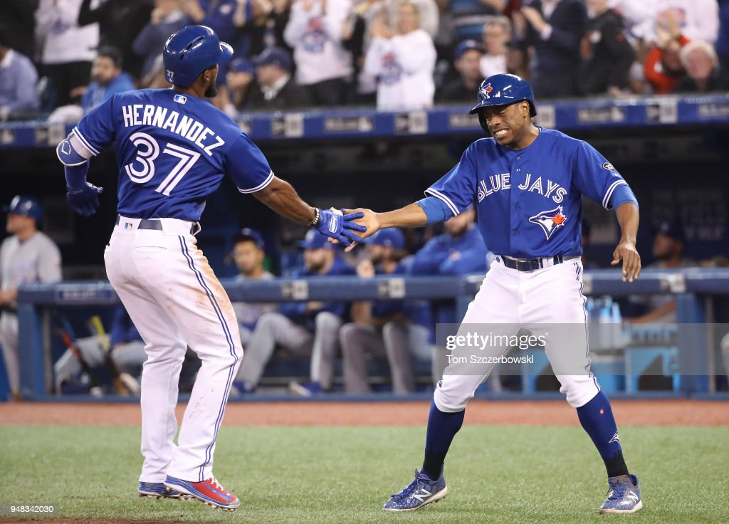 Teoscar Hernandez #37 of the Toronto Blue Jays is congratulated by Curtis Granderson #18 after hitting a two-run home run in the third inning during MLB game action against the Kansas City Royals at Rogers Centre on April 18, 2018 in Toronto, Canada.