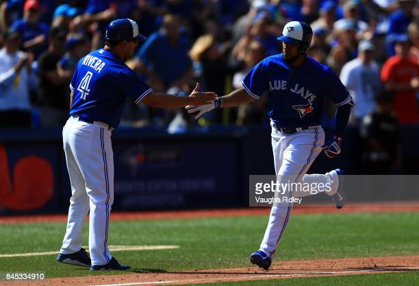 Teoscar Hernandez of the Toronto Blue Jays is congratulated by third base coach Luis Rivera after hitting his second home run of the game in the...