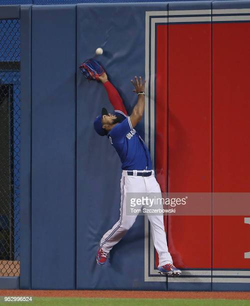 Teoscar Hernandez of the Toronto Blue Jays makes a fielding error as he misses a catch on a deep fly ball to the wall in the second inning during MLB...