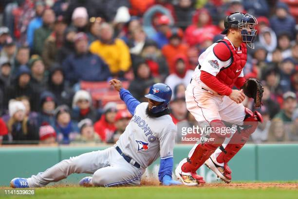Teoscar Hernandez of the Toronto Blue Jays scores a run past Christian Vazquez of the Boston Red Sox during the seventh inning of the Red Sox home...