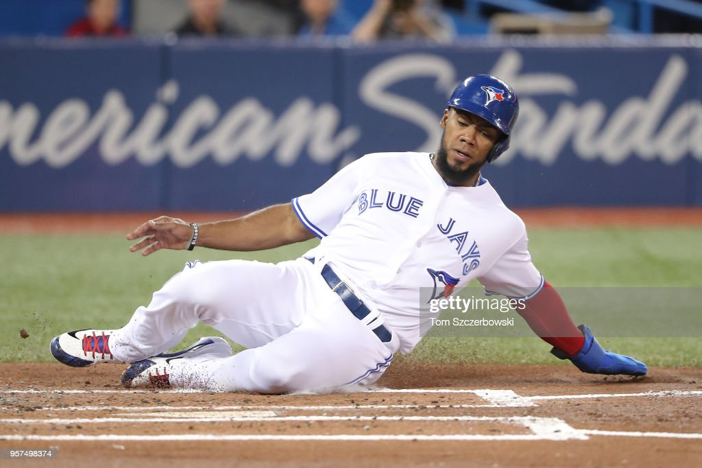 Teoscar Hernandez #37 of the Toronto Blue Jays slides across home plate to score a run in the first inning during MLB game action against the Boston Red Sox at Rogers Centre on May 11, 2018 in Toronto, Canada.