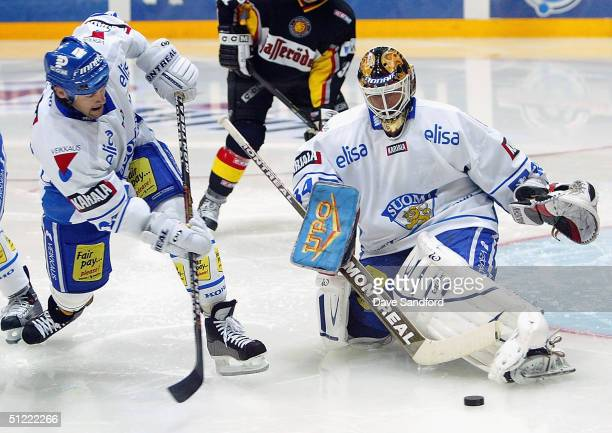 Teppo Numminen of Team Finland clears the puck after Miikka Kiprusoff also of Team Finland makes a save against Team Germany during an exhibition...