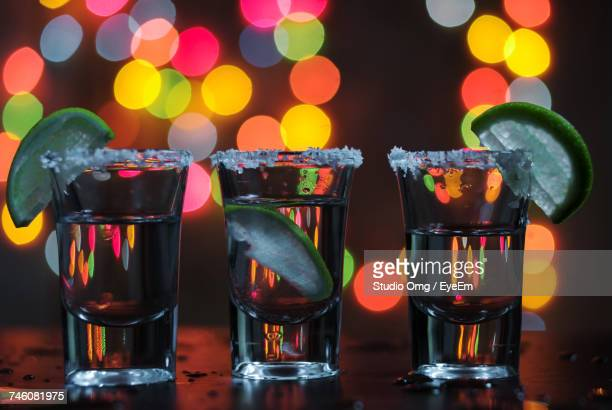 Tequila Shots Against Abstract Lights At Bar