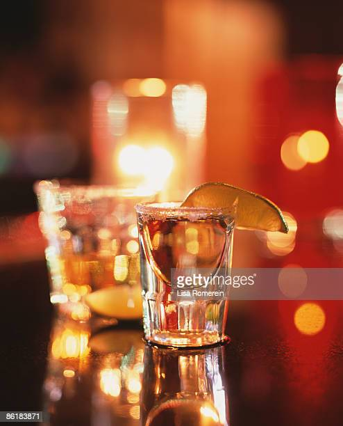 Tequila shots on the bar with salt, lime & candle