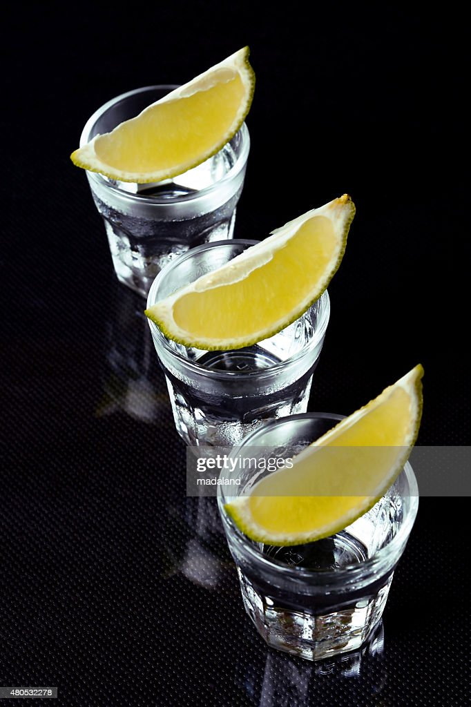 Tequila with lime on black background. : Stock Photo