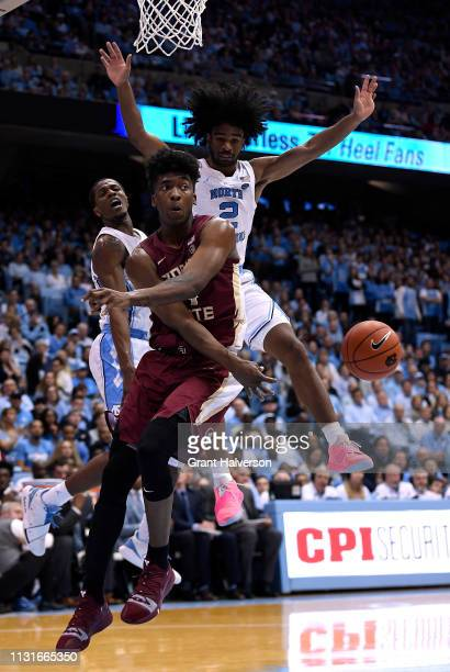Terance Mann of the Florida State Seminoles looks to pass as he drives against Coby White of the North Carolina Tar Heels during the first half of...