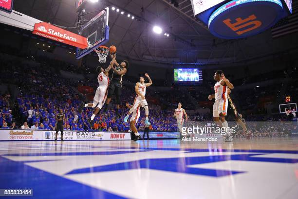 Terance Mann of the Florida State Seminoles scores in front of Kevarrius Hayes and Chris Chiozza of the Florida Gators during a NCAA basketball game...