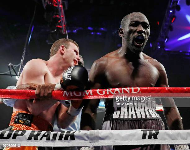 Terence Crawford celebrates his ninthround TKO victory over Jeff Horn who is held by referee Robert Byrd at the end of their WBO welterweight title...