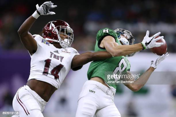 Terence Dunlap of the Troy Trojans breaks up a pass intended for Rico Bussey Jr #8 of the North Texas Mean Green during the first half of the RL...
