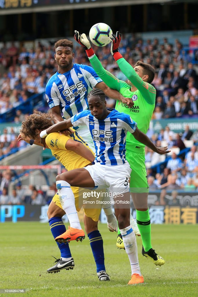 Terence Kongolo of Huddersfield (C) and Steve Mounie of Huddersfield (L) challenge Chelsea goalkeeper Kepa Arrizabalaga for the ball during the Premier League match between Huddersfield Town and Chelsea at the John Smith's Stadium on August 11, 2018 in Huddersfield, England.