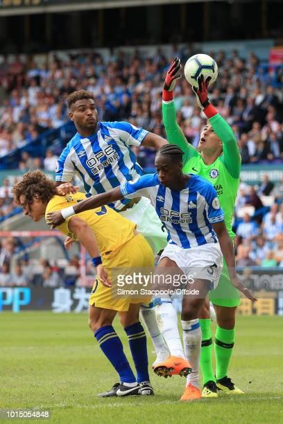 Terence Kongolo of Huddersfield and Steve Mounie of Huddersfield challenge David Luiz of Chelsea Chelsea goalkeeper Kepa Arrizabalaga for the ball...