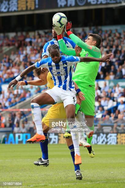 Terence Kongolo of Huddersfield and Steve Mounie of Huddersfield challenge Chelsea goalkeeper Kepa Arrizabalaga for the ball during the Premier...