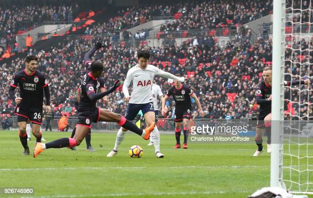 Terence Kongolo of Huddersfield stretches across HeungMin Son of Tottenham during the Premier League match between Tottenham Hotspur and Huddersfield...
