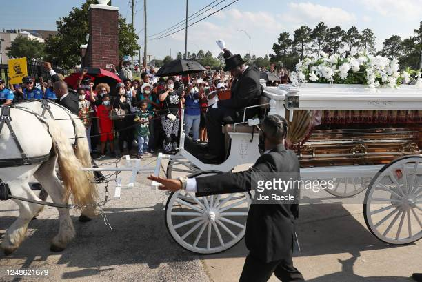 Terence Reed jr raises his arm as he drives his horse drawn hearse containing the remains of George Floyd into the Houston Memorial Gardens cemetery...