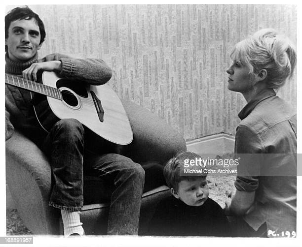 Terence Stamp holds a guitar with a boy and Carol White in a scene from the film 'Poor Cow' 1967