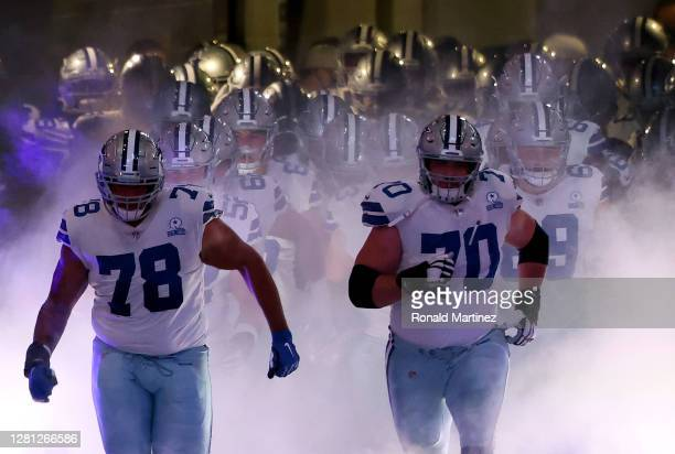 Terence Steele of the Dallas Cowboys and Zack Martin of the Dallas Cowboys lead the team out of the tunnel before a game against the Arizona...