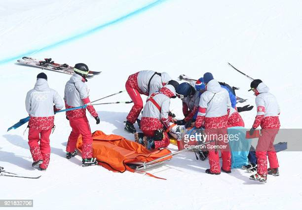 Terence Tchiknavorian of France is helped by the emergency services after a crash in the Freestyle Skiing Men's Ski Cross 1/8 finals on day 12 of the...