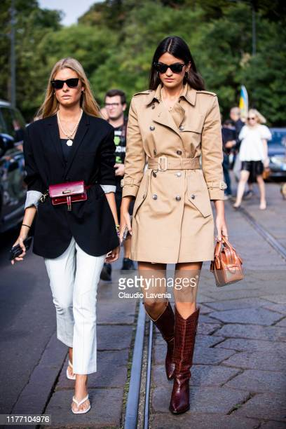 Teresa Andres Gonzalvo , wearing a black blazer, red Tod's belt bag, white pants and white sandals, and Marta Lozano , wearing a beige trench coat,...