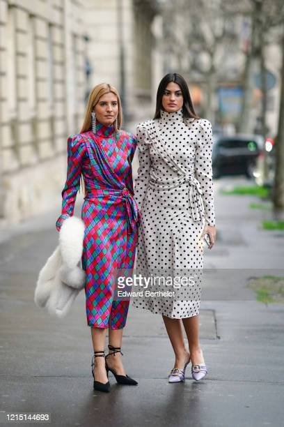Teresa Andres Gonzalvo wears long bejeweled earrings, a colored turtleneck lustrous long silky dress with printed argyle geometric patterns, a white...