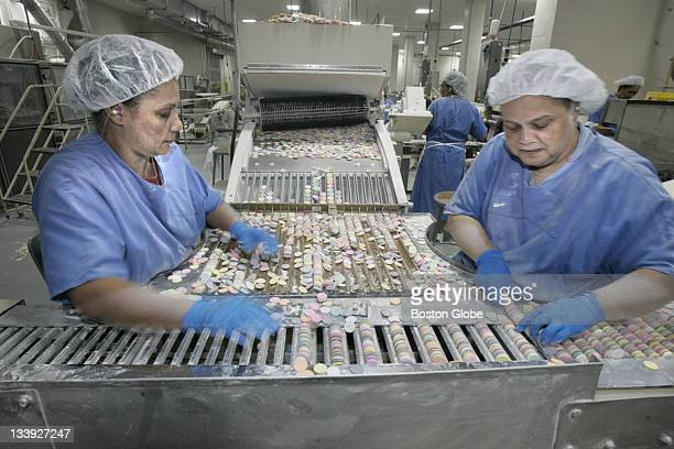 Teresa Barbosa left and Carolyn DeGraffenreid right process NECCO wafers at the New England Confectionery Company factory floor
