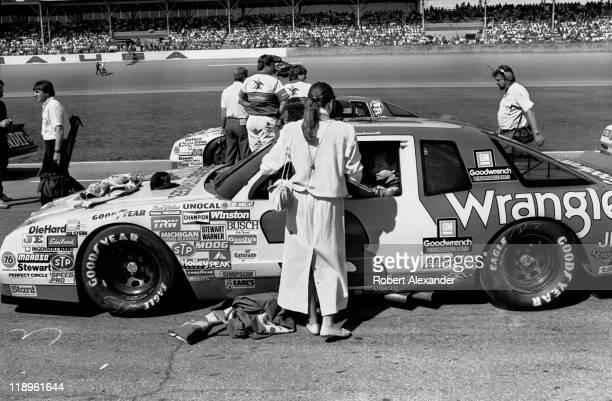 Teresa Earnhardt talks with her husband NASCAR driver Dale Earnhardt as the drivers prepare for the start of the 1987 Daytona 500 on February 15 1987...