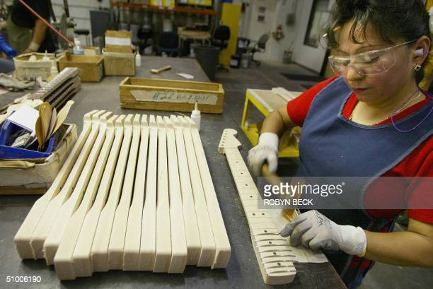 Teresa Quintero hammers frets onto necks for Fender Stratocaster guitars at the Fender manufacturing facility in Corona California 28 June 2004 The...