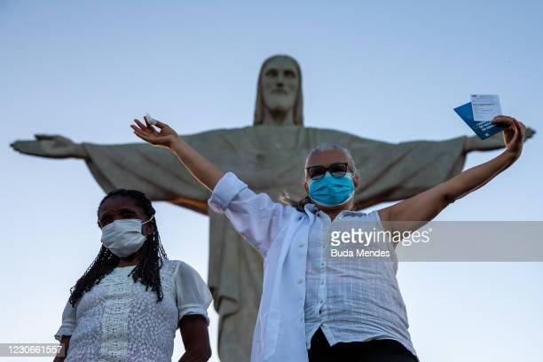 Terezinha da Conceicao and Dulcinea da Silva Lopes, 59 celebrate after receiving he CoronaVac vaccination shot at the feet of the statue of Christ...