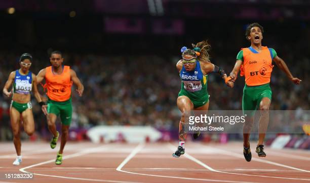 Terezinha Guilhermina of Brazil and guide Guilherme Soares de Santana cross the line to win gold ahead of silver medallists Jerusa Gerber Santos of...