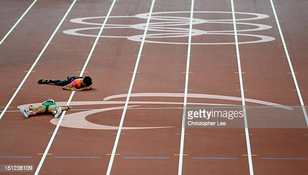 Terezinha Guilhermina of Brazil and her guide Guilherme Soares de Santana lie on the track after falling in the Women's 400m - T12 Final on day 6 of...