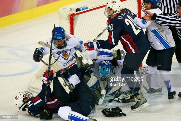 Terhi Mertanen of Finland is pushed by Katie King of the United States and trips over Kristin King also of the United States during the women's ice...