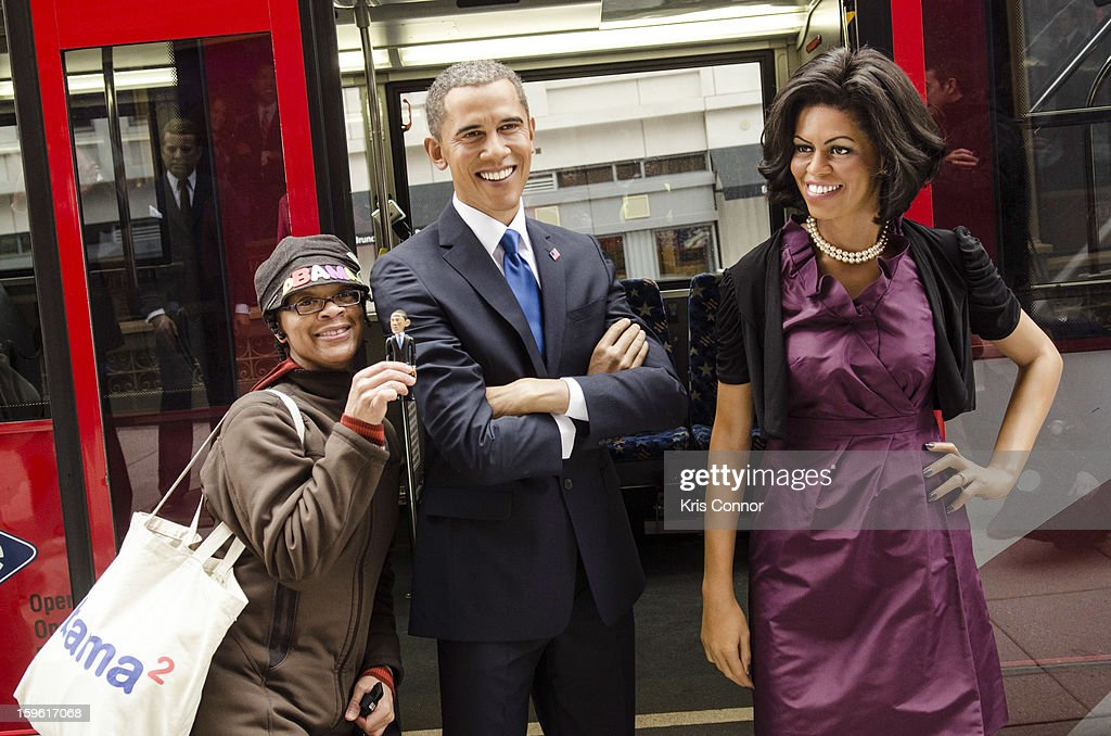 Teri Mcclain of Seattle poses with wax figures of President Barack Obama and first lady Michelle Obama during the Madame Tussauds DC Presidential Wax Figures Bus Tour on January 17, 2013 in Washington, United States.